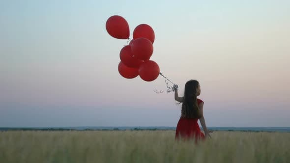 Thumbnail for Happy Girl with Balloons Running in the Wheat Field at Sunset.