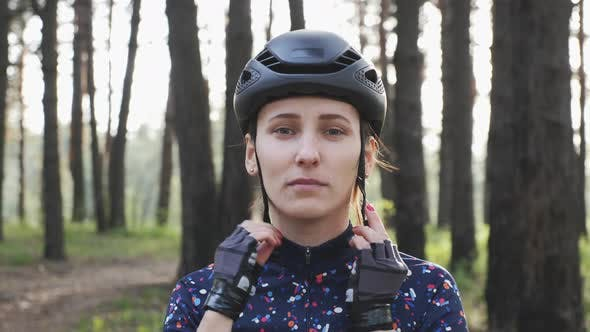 Woman wears black helmet before bicycle ride