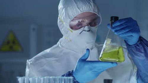 Male Virology Scientist Examining Yellow Liquid in Glass Flask