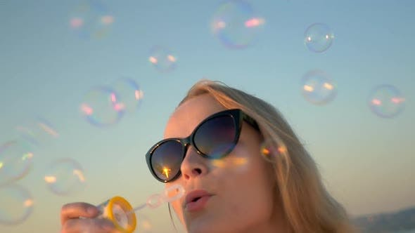 Young Woman in Sunglasses Blowing Soap Bubbles