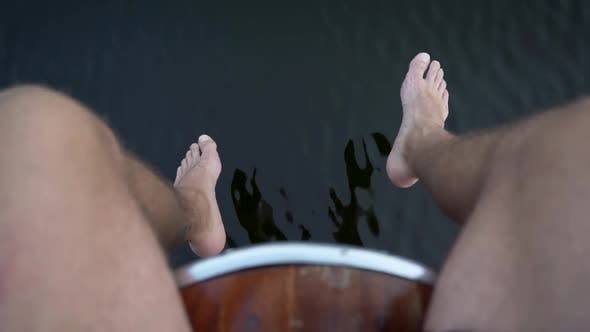 Thumbnail for Man Swinging Barefoot Legs Above Water