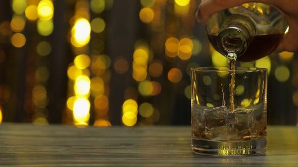 Thumbnail for Pouring of Golden Whiskey, Cognac or Brandy From Bottle Into Glass with Ice Cubes. Shiny Background