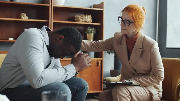 Female Counseling Psychologist Supporting Stressed Black Man