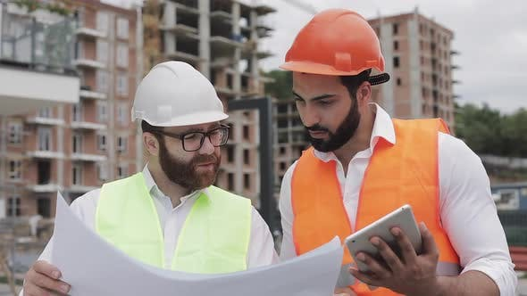 Thumbnail for Building a Residential Complex or Business Center. Team of Engineers Men with a Tablet and Drawing