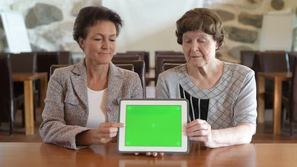 Cover Image for Happy Mother And Daughter Showing Digital Tablet Together At The Coffee Shop