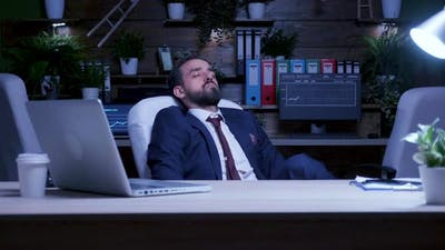Late at Night in the Office a Businessman is Sleeping