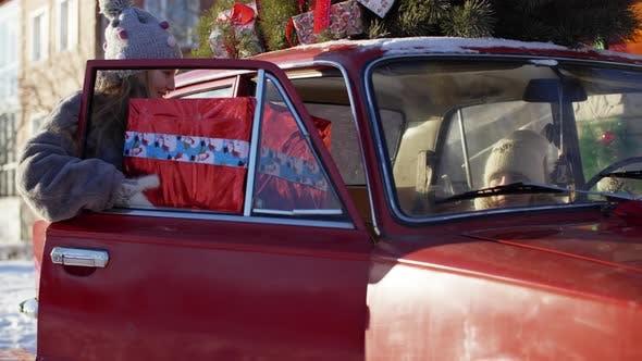 Thumbnail for Glückliches kleines Mädchen legt Neujahrsgeschenk Box in das Auto mit geschmücktem Weihnachtsbaum. Fröhliches Mädchen