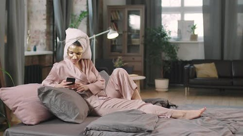 Young Woman In Gold Sheet Mask Chilling On Bed