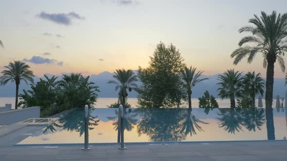 Outdoor swimming pool on resort Scene with nature background at sunset