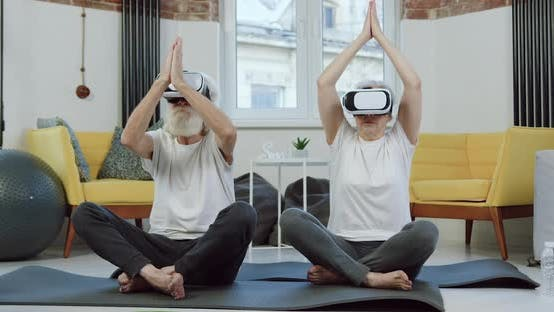 Thumbnail for Mature Couple in Virtual Reality Headset which Doing Yoga Exercises while Training at Home