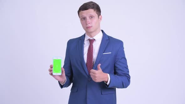 Cover Image for Happy Young Handsome Businessman Showing Phone and Giving Thumbs Up
