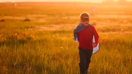 Thumbnail for A Boy in a Suit and a Superhero Mask Running Across the Field at Sunset on the Grass