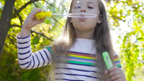 Thumbnail for Close-up of a Nice Brunette Girl Staying in Autumn Sundays and Blowing Soap Bubbles