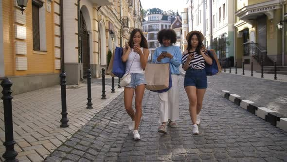 Cover Image for Young Women Walking with Phones and Shopping Bags