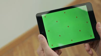 Male Hand Holding Tablet with Green Screen. Man Reading Ebook with Green Screen