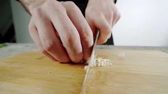 Thumbnail for Male Cheff Hands Cutting Garlic with a Lknife on a Wooden Cutting Board. Close Up. Slow Motion