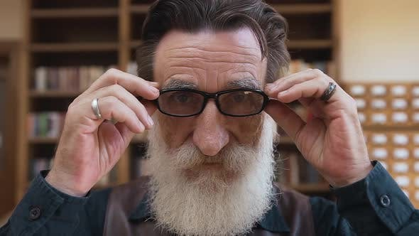 Thumbnail for Bearded Man with Wrinkled Face Putting on His Eyeglasses and Posing on Camera