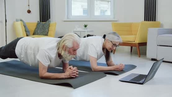 Senior Couple Doing Elbow Plank at Home and Simultaneously Revisioning Video Lessons