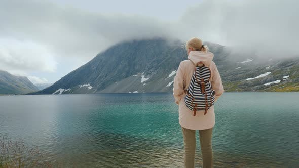 Thumbnail for A Woman Admires a Beautiful High Mountain Lake in the Mountains of Norway