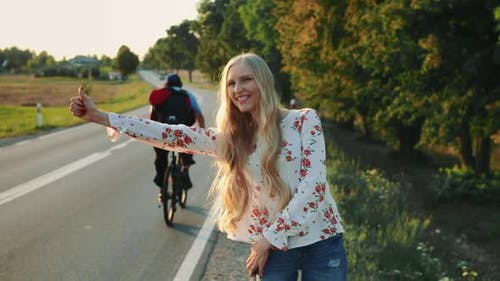 Young Lady Hitchhiking on Countryside Road.
