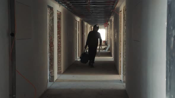 Silhouette of a Construction Worker Walking Down a Dark Corridor with a Tool in His Hands