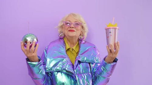 Smiling Elderly Woman Holding Two Cocktails As She Poses for the Camera Standing Against an Isolated