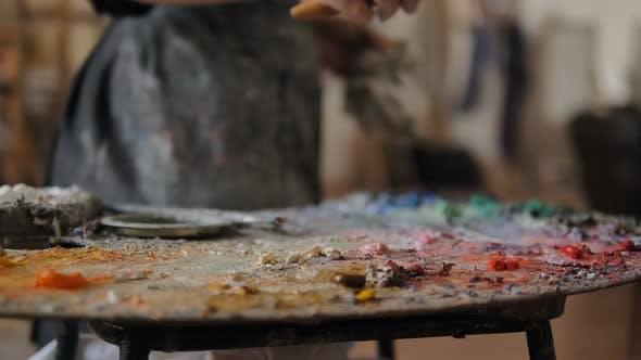 Thumbnail for Lady nimmt Farbe aus Palette zum Auftragen auf Leinwand im Studio