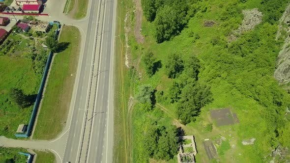Thumbnail for Aerial: Flying Over the Highway in Mountain Conditions. Also View of Small Tourist Town.