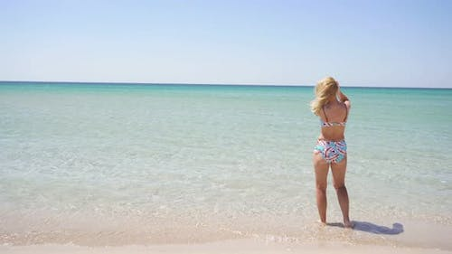 Rear View of an Unrecognizable Woman in a Bathing Suit Standing in the Azure Sea Looking Around