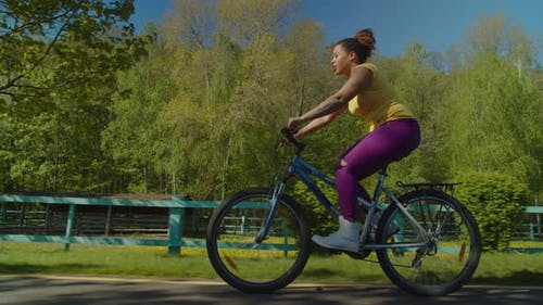Pretty Black Woman Enjoying Active Lifestyle Riding on Bicycle Outdoors
