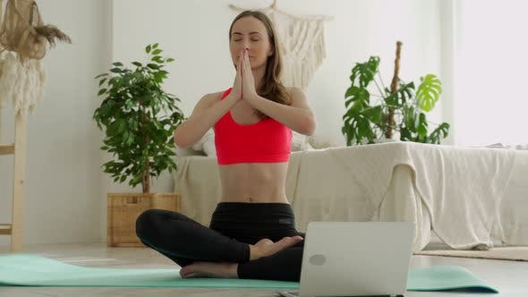 Positive Yoga Woman Does Practice in Front of a Laptop While Sitting on a Sports Mat at Home