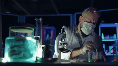 Chemist Looks Through a Microscope Picks Up the Reagent in a Pipette and Drips Onto the Glass
