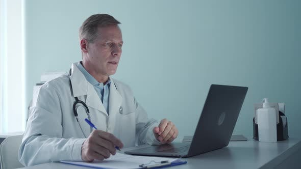 Senior Old Male Doctor Consulting Patient Online By Video Call on Laptop