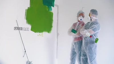 People in Protective Suits Displeased of Strokes on Wall