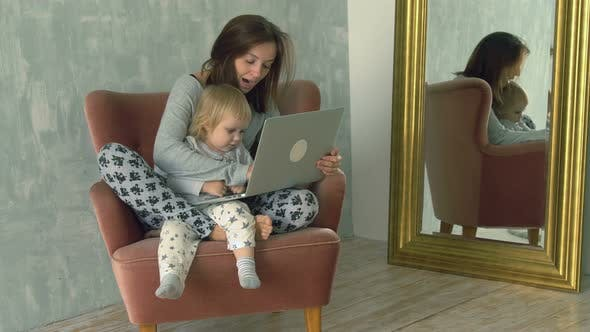 Thumbnail for Pretty woman using laptop with little baby on her knees