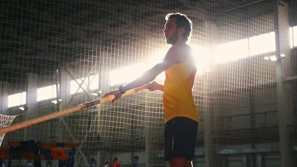 Thumbnail for Pole Vaulting Indoors - a Man in Yellow Shirt Standing on the Track with a Pole and Preparing for