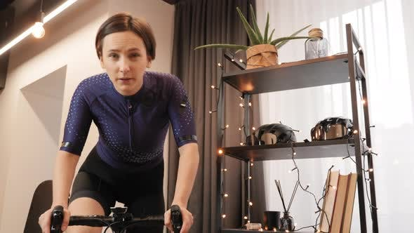 Professional cyclist is finishing online bicycle race, pedaling out of saddle. Indoor cycling