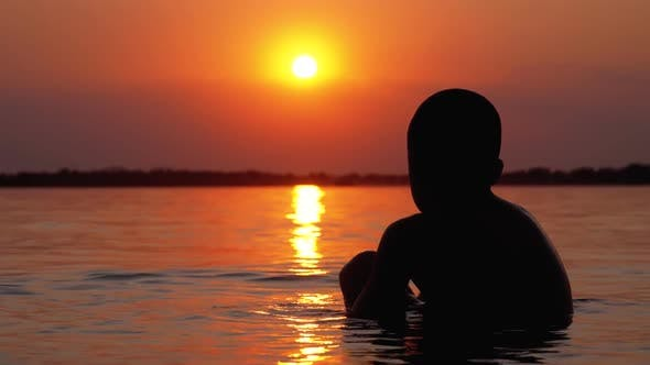 Silhouette of Boy Sitting in the Water on Background of Sunset and Orange Path. Slow Motion