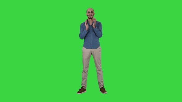 Thumbnail for Young Arabic Man Standing Claps His Hands Smiling on a Green Screen, Chroma Key
