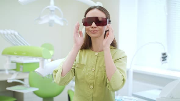 Thumbnail for Young Woman Dressing Up UV Orange Safety Glasses. Portrait of Dentist