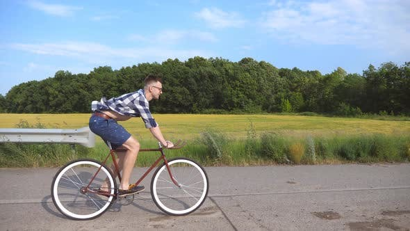 Thumbnail for Young Handsome Man Riding at Vintage Bicycle in the Country Road. Sporty Guy Cycling at the Track