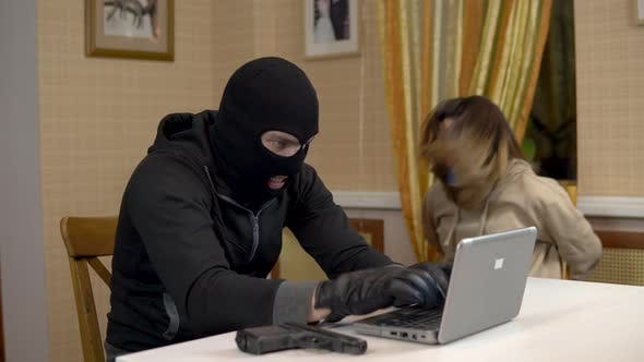 Thumbnail for A Burglar Is Trying To Break Into a Laptop By Taking a Young Woman Hostage. A Masked Thug Sits in a
