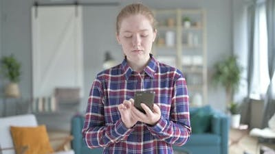 Young Woman Standing And Using Smart Phone