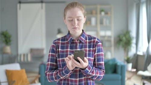 Junge Frau stehend und mit Smartphone
