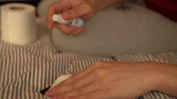 Human Hand Spraying Alcohol Sanitizer on Mobile Phone to Prevent Infection of Covid19 Virus
