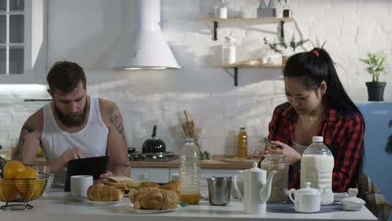 Thumbnail for Couple Busy Using Gadgets in the Kitchen