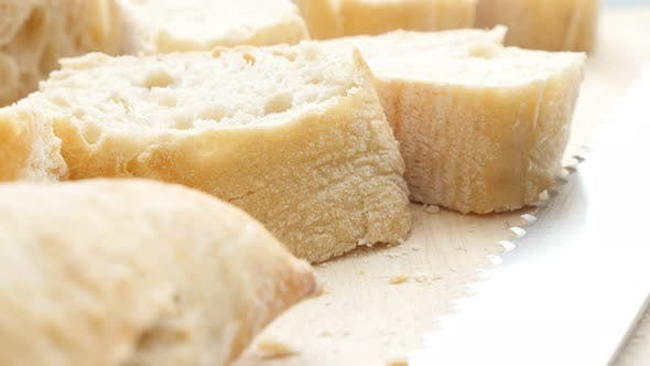 Thumbnail for Laib Französisch Baguette Brot geschnitten auf kleinere Stücke 4K 2160p 30fps UltraHD Filmmaterial - Traditionell