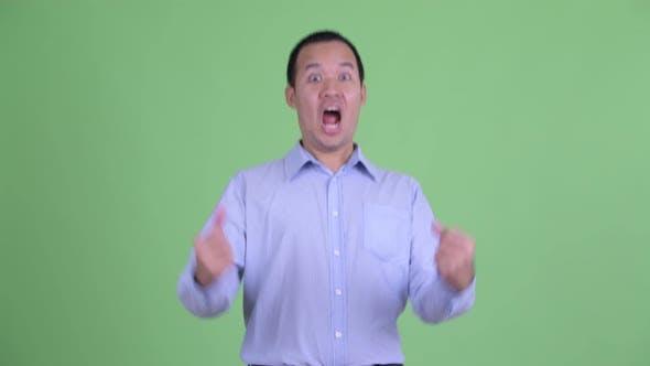 Thumbnail for Studio Shot of Happy Asian Businessman Getting Good News
