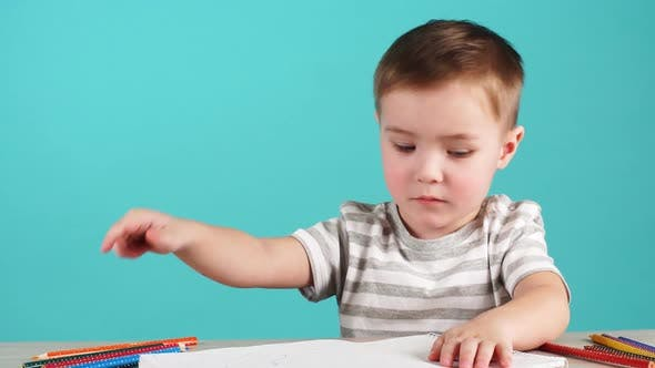 Cover Image for Inspired Little Boy at the Table Draw with Pencils, Isolated on Blue