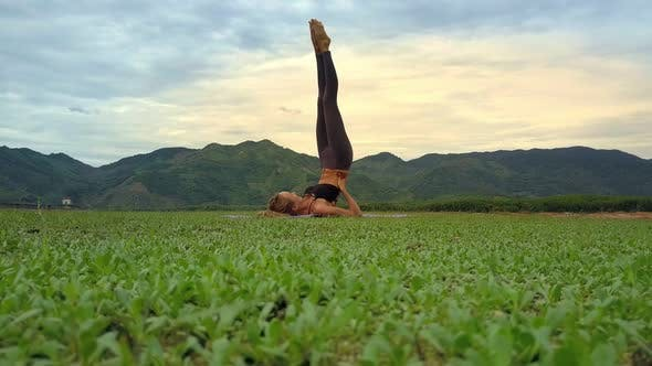 Thumbnail for Drone Shows Girl Holding Yoga Pose Against Landscape of Hills